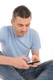 Hombre joven ocasional que envía sms en el teléfono Fotografía de archivo libre de regalías