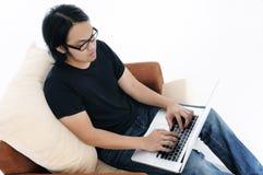 Hombre joven ocasional que usa la computadora portátil Fotos de archivo libres de regalías