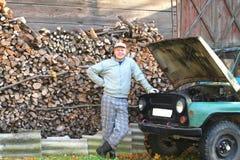 Hombre joven orgulloso de su coche viejo Imagen de archivo libre de regalías