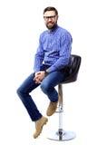 Hombre joven orgulloso y satisfecho que se sienta en silla y que mira la cámara aislada en blanco Imagen de archivo libre de regalías