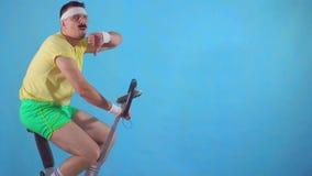 Hombre joven a partir de años 80 con el bigote en el pulgar azul de la demostración del fondo del bikeon del ejercicio abajo del  almacen de video