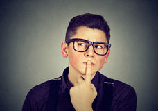 Hombre joven pensativo aislado en fondo gris Imagen de archivo libre de regalías
