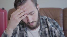 Hombre joven pensativo barbudo hermoso del retrato del primer en una camisa de tela escocesa dentro almacen de video