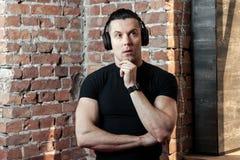 Hombre joven pensativo con los auriculares Imagen de archivo libre de regalías