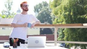 Hombre joven pensativo de pensamiento, café de consumición que se coloca en el balcón al aire libre almacen de metraje de vídeo