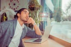 Hombre joven pensativo delante del ordenador portátil que mira para echar a un lado pensativo imágenes de archivo libres de regalías