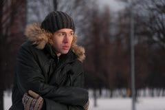 Hombre joven pensativo en el parque del invierno Imagen de archivo libre de regalías