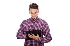 Hombre joven pensativo que hace papeleo Imagenes de archivo