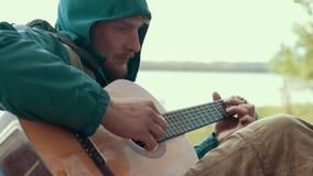Hombre joven pensativo que juega música en la guitarra acústica de las secuencias metrajes