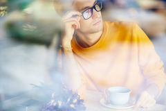 Hombre joven pensativo que mira fuera de ventana del café imagen de archivo libre de regalías
