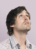 Hombre joven pensativo que mira para arriba Foto de archivo libre de regalías