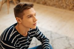 Hombre joven pensativo que se sienta en el piso Fotografía de archivo libre de regalías