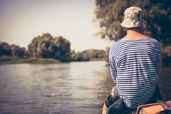 Hombre joven pensativo que viaja en el barco y que mira en paisaje hermoso durante días de fiesta del campamento de verano Imagenes de archivo