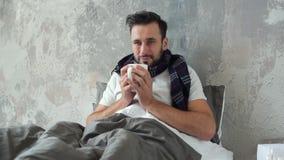 Hombre joven pobre que bebe té caliente mientras que siente enfermo metrajes
