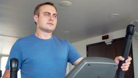 Hombre joven positivo juguetón del ajuste hermoso en el gimnasio que hace ejercicios en la elaboración elíptica del instructor almacen de video