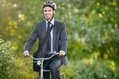 Hombre joven positivo que monta una bicicleta para trabajar Fotografía de archivo libre de regalías