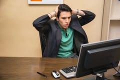 Hombre joven preocupado, preocupante que mira fijamente el ordenador imágenes de archivo libres de regalías