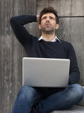 Hombre joven preocupante o aliviado con el ordenador portátil Imagenes de archivo