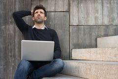 Hombre joven preocupante o aliviado con el ordenador portátil Imagen de archivo