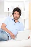 Hombre joven puesto en un sofá Imagenes de archivo
