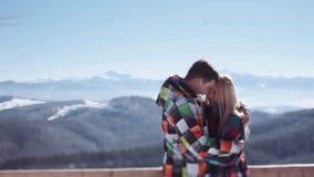 Hombre joven que abraza blando a su novia rubia atractiva mientras que se coloca en la plataforma de observación de la montaña am metrajes