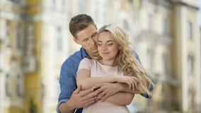 Hombre joven que abraza a la novia de detrás, besando su mano y mejilla, en amor almacen de metraje de vídeo