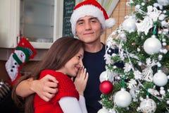 Hombre joven que abraza a su novia en la Navidad Fotografía de archivo libre de regalías