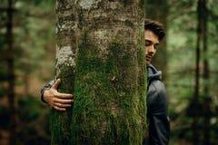 Hombre joven que abraza un árbol Foto de archivo