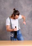 Hombre joven que abre el vino rojo Imágenes de archivo libres de regalías