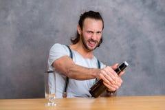 Hombre joven que abre una botella de cerveza Fotografía de archivo libre de regalías