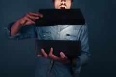 Hombre joven que abre una caja emocionante Imágenes de archivo libres de regalías