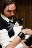 Hombre joven que acaricia el gato Foto de archivo libre de regalías