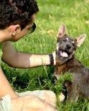 Hombre joven que acaricia un perrito Fotografía de archivo