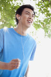 Hombre joven que activa mientras que escucha la música Imágenes de archivo libres de regalías