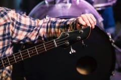 Hombre joven que adapta la guitarra eléctrica Cierre para arriba Imágenes de archivo libres de regalías
