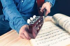 Hombre joven que adapta una guitarra Imágenes de archivo libres de regalías