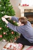Hombre joven que adorna el árbol de navidad en casa con la chimenea. Fotos de archivo libres de regalías