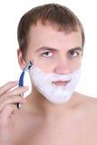 Hombre joven que afeita con la maquinilla de afeitar Fotografía de archivo libre de regalías