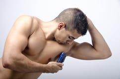 Hombre joven que afeita su axila Fotografía de archivo