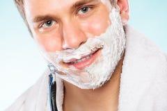 Hombre joven que afeita usando la maquinilla de afeitar con la espuma poner crema Fotografía de archivo libre de regalías