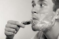 Hombre joven que afeita usando la maquinilla de afeitar con la espuma poner crema Foto de archivo libre de regalías