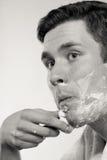 Hombre joven que afeita usando la maquinilla de afeitar con la espuma poner crema Imagen de archivo libre de regalías
