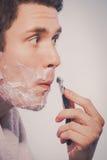 Hombre joven que afeita usando la maquinilla de afeitar con la espuma poner crema Foto de archivo