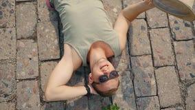 Hombre joven que agita con un sombrero para refrescarse abajo debido al calor en la cámara lenta almacen de metraje de vídeo
