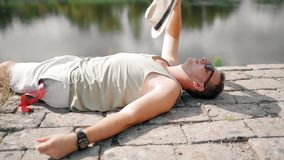 Hombre joven que agita con un sombrero para refrescarse abajo debido al calor en la cámara lenta almacen de video