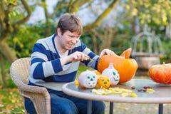 Hombre joven que ahueca hacia fuera una calabaza para preparar la linterna de Halloween Fotos de archivo
