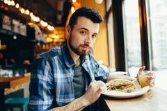 Hombre joven que almuerza en el café Imagen de archivo libre de regalías