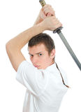 Hombre joven que amenaza con la espada. Imagen de archivo libre de regalías
