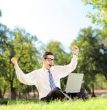 Hombre joven que anima y que ve la TV en un ordenador portátil en un parque en un su Imagen de archivo