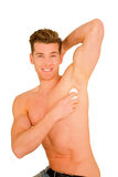 Hombre joven que aplica el desodorisante Fotografía de archivo libre de regalías